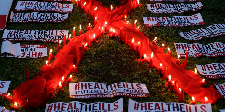 An HIV-positive Filipino lights candles around an AIDS symbol as he participates in an event in observance of World AIDS Day in Quezon city, Philippines.