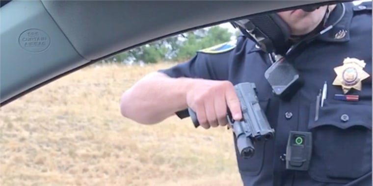 Image: A cop points a gun at a passenger on on Highway 101.