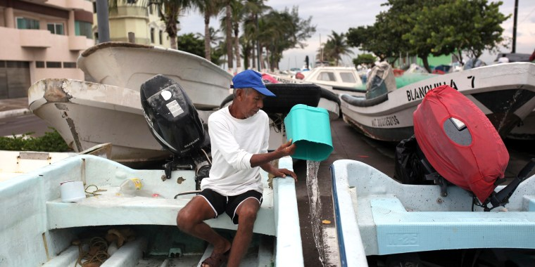 Image: A tourist boat operator bails water from out of his boat