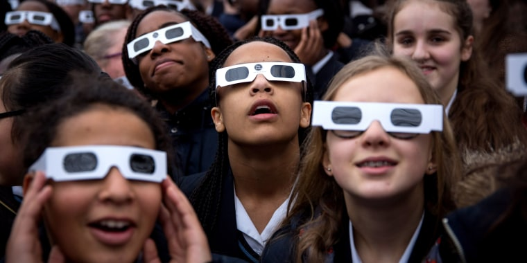 Image: Students wear protective glasses as they view a partial solar eclipse