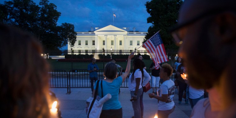 Image: People participate in a candlelight vigil at the White House
