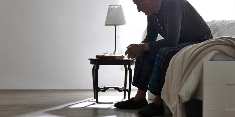 Image: Elderly Man Sitting on Bed Looking Serious