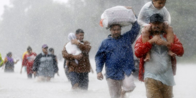 Image: Residents wade through flood waters from Tropical Storm Harvey in Beaumont Place, Houston