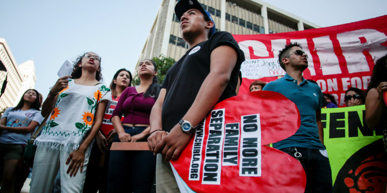 Image: Axel, 15, the son of a DACA program recipient, stands with supporters during a rally outside the Federal Building in Los Angeles