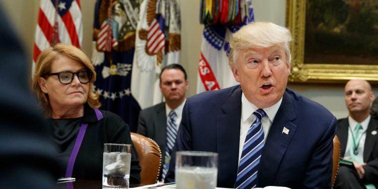 Image: President Donald Trump, seated next to Sen. Heidi Heitkamp, D-N.D.