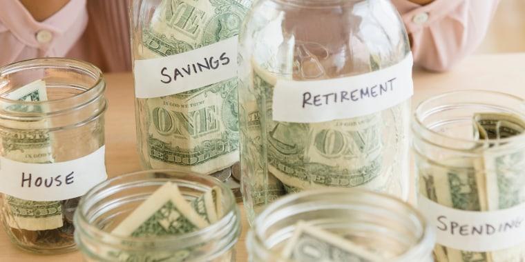 Mixed race woman putting money in savings jars