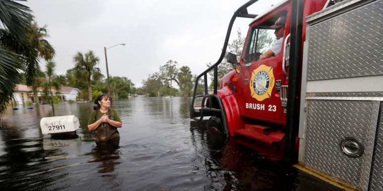 Firefighters check on Kelly McClenthen, who returned to check on the damage to her flooded home in Bonita Springs, Florida, on Monday in the wake of Hurricane Irma.