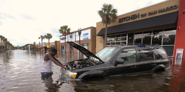Image: John Duke tries to figure out how to salvage his flooded vehicle