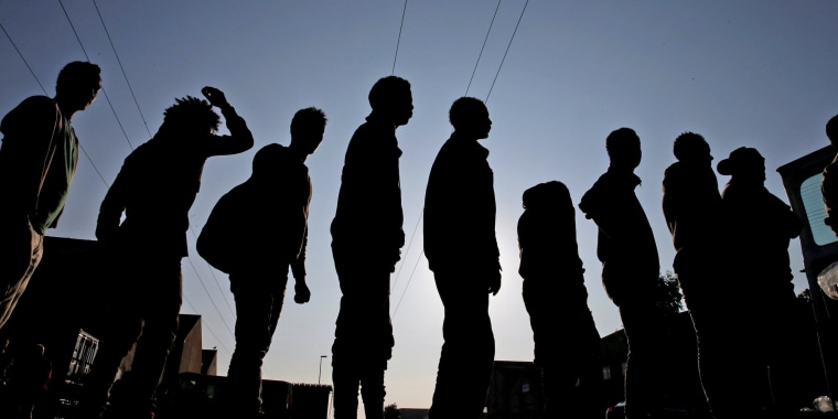 """Image: Migrants from Ethiopia and Eritrea queue in line during a food distribution near the former """"jungle"""" in Calais"""