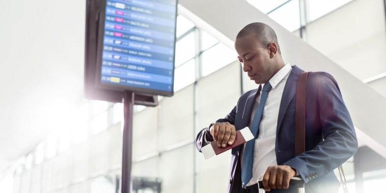 Businessman checking the time on wristwatch below arrival departure board at airport