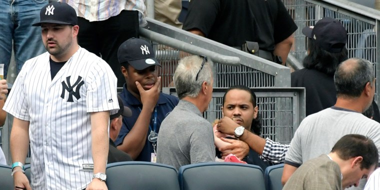Image: Baseball fans reacts as a young girl is tended to before she is carried out after being hit by a line drive