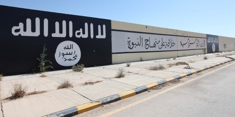 Islamic State painted flags and slogans are seen on a wall after Libyan forces allied with the U.N.-backed government captured Al-Naqa neighborhood, in Sirte