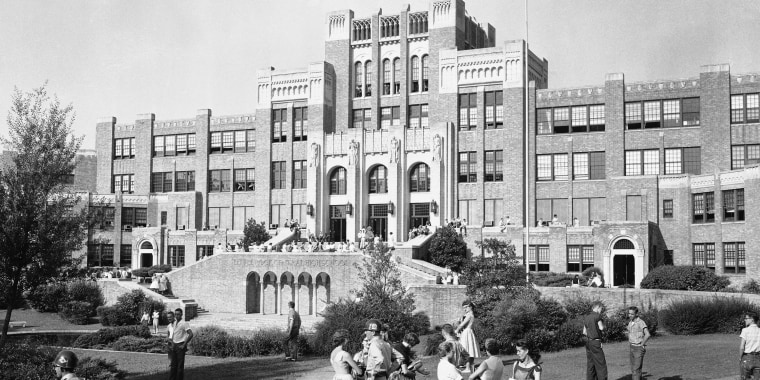 Students and members of the National Guard outside Central High School in Little Rock, Ark., weeks before nine black students entered the school protected by members of the 101st Airborne. The 60th anniversary of the Little Rock Nine's enrollment is Monday, Sept. 25, 2017. (AP Photo/William P. Straeter, File)