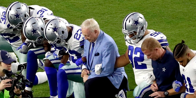 Image: The Dallas Cowboys, led by owner Jerry Jones, take a knee before the national anthem