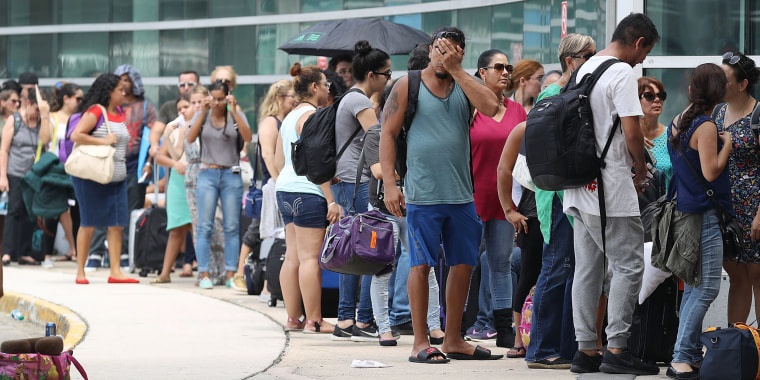 Image: People wait in line to get a flight out of the Luis Munoz Marin International Airport