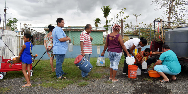 Image: People take water from a tank in Vega Baja, Puerto Rico