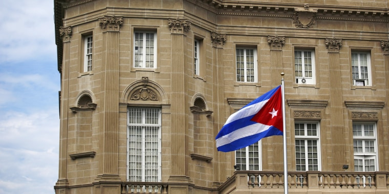 Image: Cuban national flag is seen raised over their new embassy in Washington