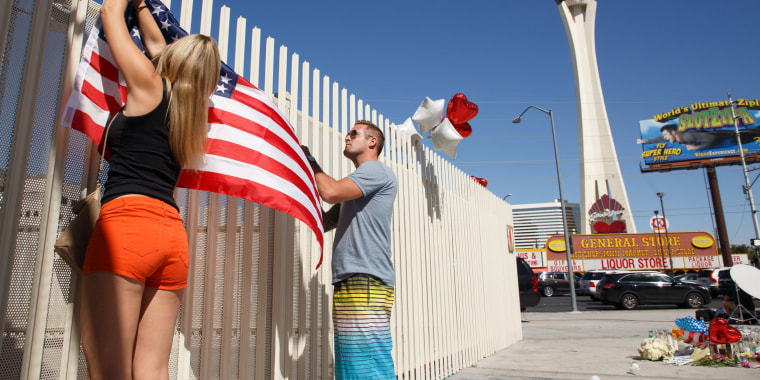 Image: Mourners put up a U.S. flag in Las Vegas