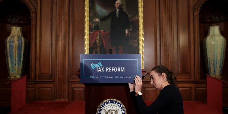 Image: A staff member sets the stage before a GOP news conference on tax reform
