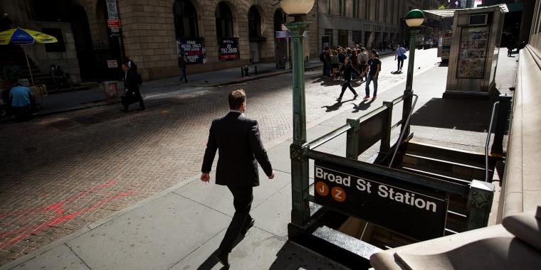 Image: A pedestrian walks along Wall Street