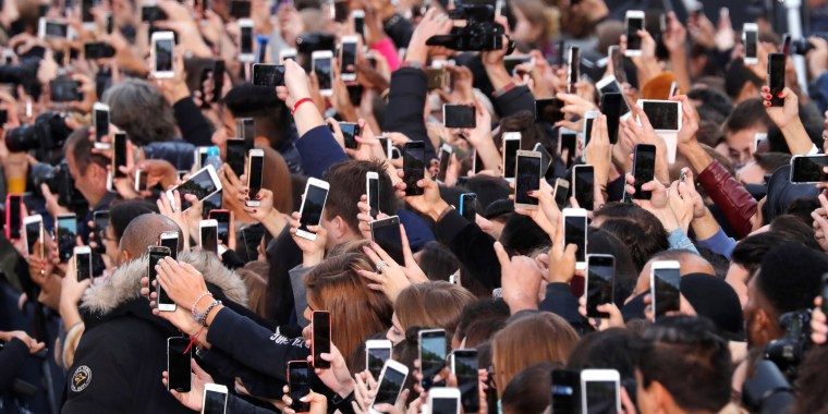 Image: People use their smartphone to take photos