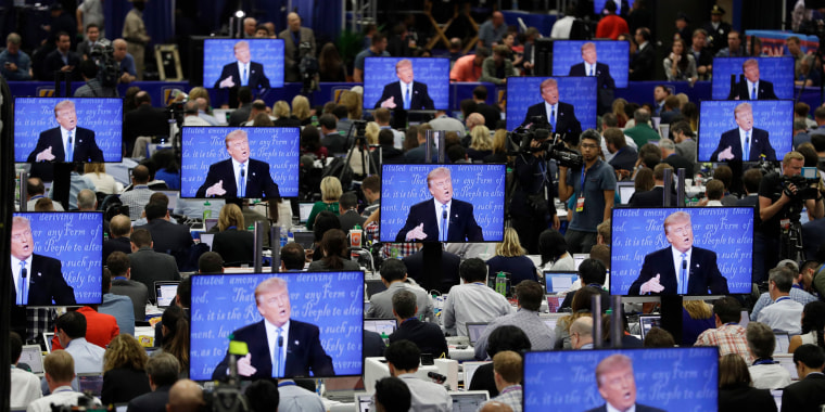 Image: Trump is seen on screens in the media center during the presidential debate