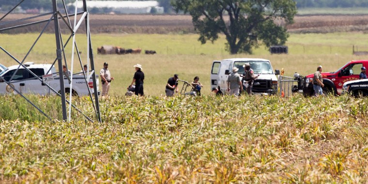 Image: The partial frame of a hot air balloon is visible above a crop field as investigators comb the wreckage of a Saturday morning accident that left 16 people feared dead when the balloon crashed in Maxwell