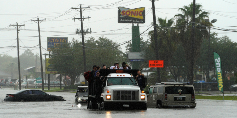 Image: People evacuate by dump truck from the Hurricane Harvey floodwaters in Dickinson, Texas, Aug. 28, 2017.