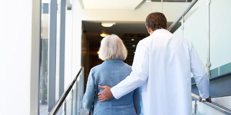 Image: A doctor assists an elderly woman along a hospital corridor