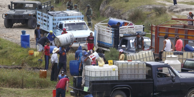 Image: People fill large drums of fuel from a clandestine outlet in San Francisco Tlaloc, Puebla state Mexico, on Oct. 23.