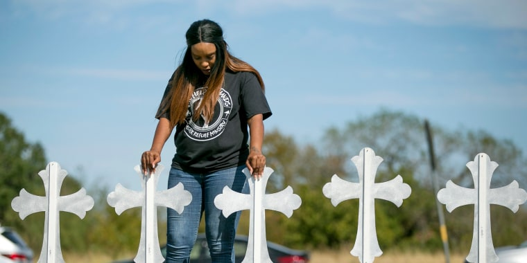 Image: Sheree Rumph of San Antonio prays over two of the 26 crosses
