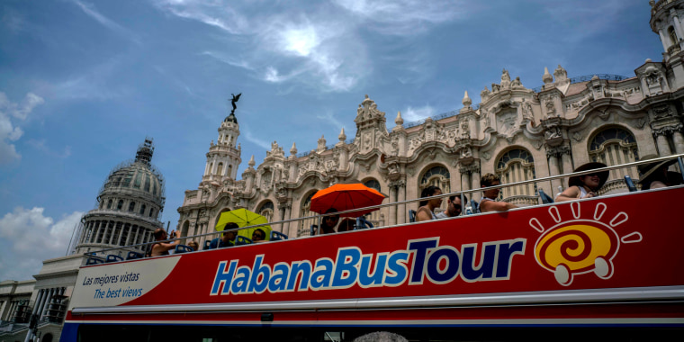 Image: Tourists ride a tour bus in front of the Capitolio in Havana