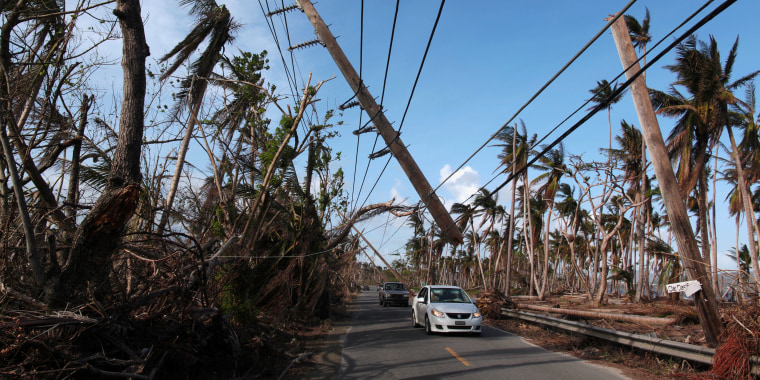 Image:Cars drive under a partially collapsed utility pole, after the island was hit by Hurricane Maria in September, in Naguabo