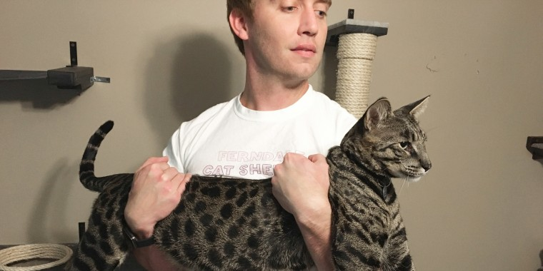 Image: Will Powers holds his cat Arcturus