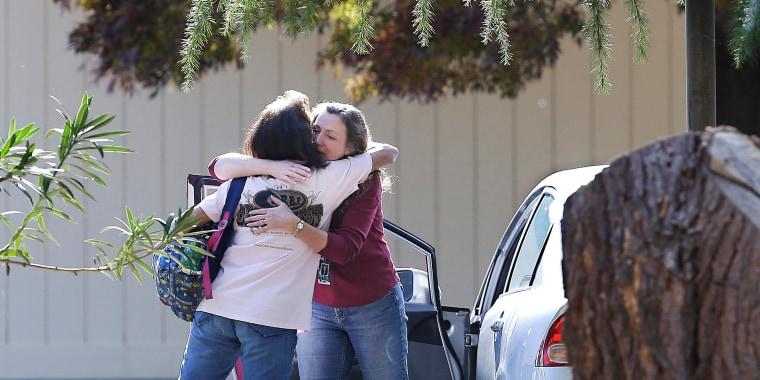 Image: Two women embrace outside Rancho Tehama Elementary School