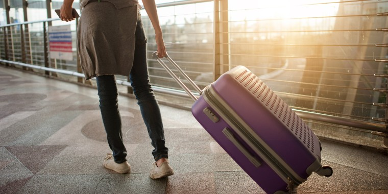 Image: Woman in airport with suitcase