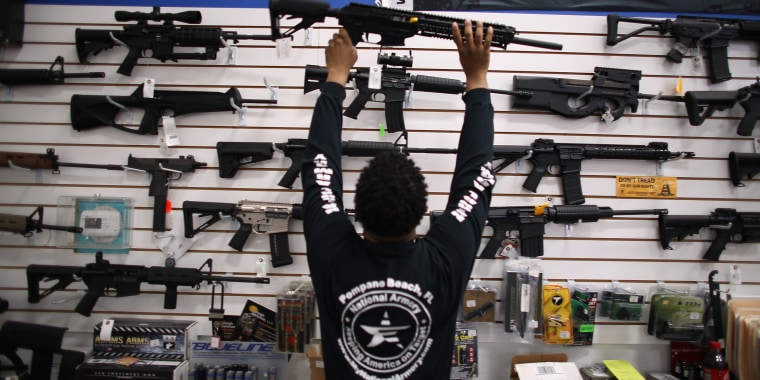 Image: Mike Acevedo Puts a Weapon on Display at the National Armory gun store