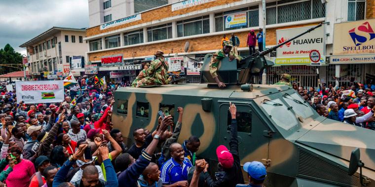 Image: People cheer a passing Zimbabwe military vehicle