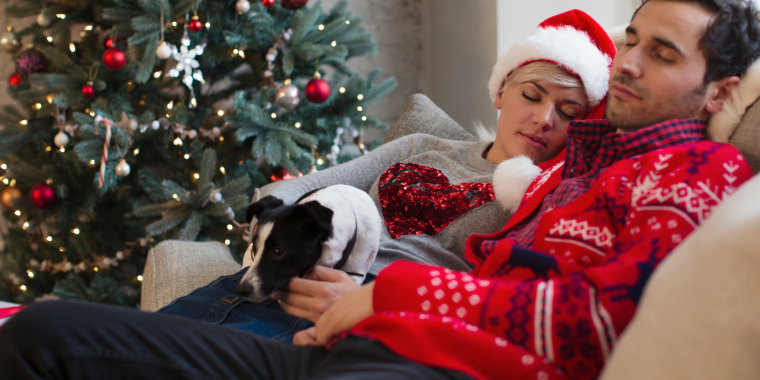 Serene couple napping with dog on sofa next to Christmas tree