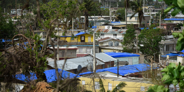 In this Oct. 19, 2017 photo, homes stand covered with FEMA tarps in the Cantera area, as the banking zone stands in the background in San Juan, Puerto Rico.