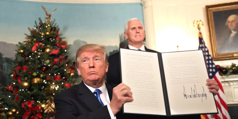 Image: Vice President Mike Pence, right, watches as President Donald J. Trump holds up his proclamation