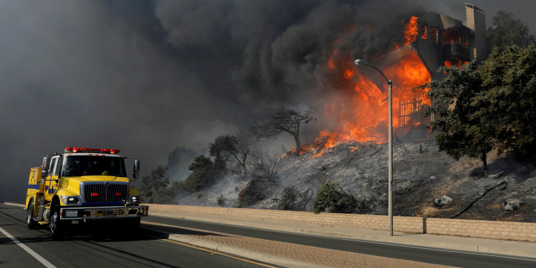 Image: FILE PHOTO: A fire crew passes a burning home during a wind-driven wildfire in Ventura, California