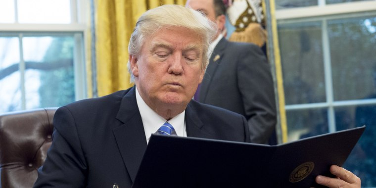 Image: U.S. President Donald Trump reads an executive order