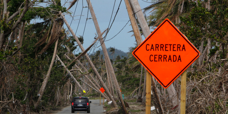 Image: A car drives under downed power lines in the aftermath of Hurricane Maria