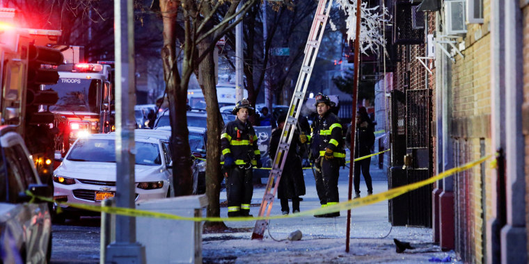 Image: Fire Department of New York (FDNY) personnel work on the scene of an apartment fire in Bronx, New York