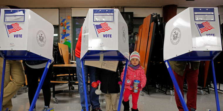 Image: Myla Gibson, 3, waits as her father Ken Gibson fills out a ballot for the U.S presidential election at the James Weldon Johnson school in the East Harlem neighbourhood of Manhattan, New York City