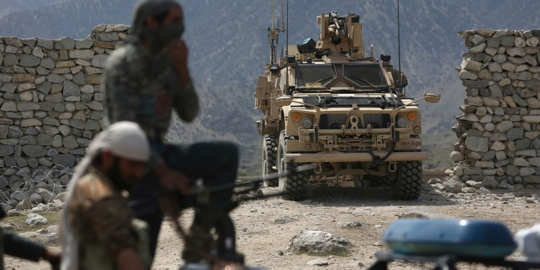 Image: U.S. forces and Afghan security police are seen near the site of a U.S. bombing in Achin, Afghanistan