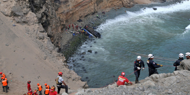 Image: Rescue workers  and police work at the scene after a bus crashed with a truck and careened off a cliff along a sharply curving highway north of Lima