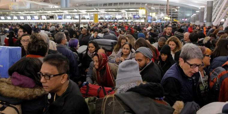 Image: Large crowds try to make their way through the departures area of Terminal 4 at John F. Kennedy International Airport following a series of delayed and canceled flights and a water main break in New York City