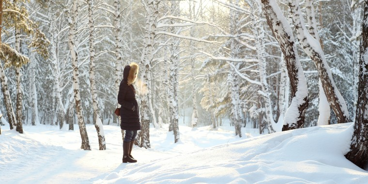 Image: Side View Of Woman Standing Against Bare Trees On Snow Covered Field At Forest